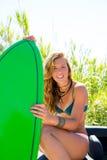 有绿色冲浪板的白肤金发的青少年的冲浪者女孩在汽车 图库摄影