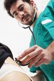 有绿色制服的医生支持与听诊器的听诊 免版税图库摄影
