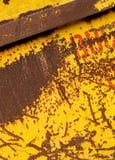 有黄色发隆隆声的油漆的老生锈的金属跳容器 库存照片