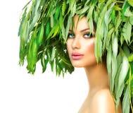 有绿色叶子的女孩在她的头 库存照片
