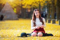 有黄色叶子的美丽的女孩在娜米海岛,韩国 免版税图库摄影