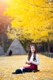 有黄色叶子的美丽的女孩在娜米海岛 免版税库存照片