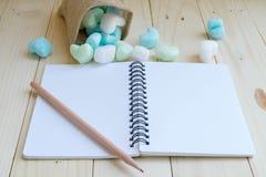 有绿色和蓝色心脏的空白的笔记本从大袋和铅笔 库存图片