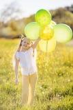 有绿色和黄色气球的小愉快的女孩 图库摄影