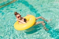 有黄色圆环的性感的女孩在池边聚会 库存照片