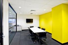 有黄色墙壁和电视的小会议室 库存图片
