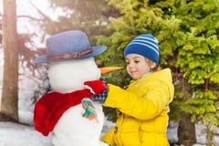 有黄色外套的小男孩在公园做雪人 免版税图库摄影