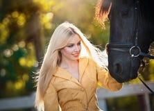有黄色外套的时兴的夫人在黑马附近在森林里 免版税库存图片