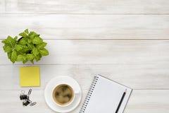 有绿色室内植物、咖啡,开放空白的笔记本和黑铅笔的办公室工作场所 免版税库存照片
