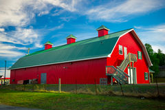 有绿色屋顶的长的红色谷仓 免版税库存照片