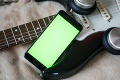 有绿色屏幕的智能手机在一把电吉他吉他 库存照片
