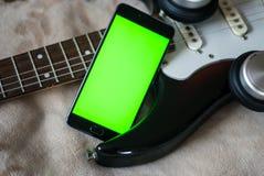 有绿色屏幕的智能手机在一把电吉他吉他 免版税库存照片