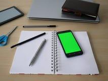 有绿色屏幕的智能手机在笔记本说谎 在背景、办公用品和事务中 免版税图库摄影