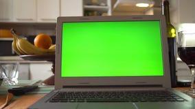 有绿色屏幕的膝上型计算机在厨房用桌上 影视素材