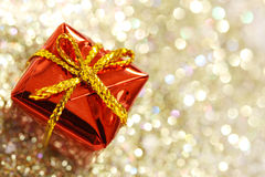 有黄色弓的圣诞节红色礼物盒在闪烁银和金背景 免版税库存照片