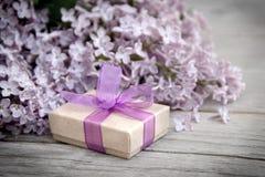 有紫色弓的在木头的礼物盒和丁香 免版税库存照片