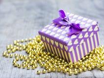 有黄色心脏的紫色礼物盒在金黄珍珠 库存照片