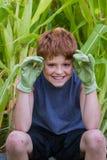 有绿色手套的年轻男孩 免版税库存图片