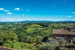 有绿色托斯坎小山的房子概要在背景和蓝天中在圣吉米尼亚诺 库存照片