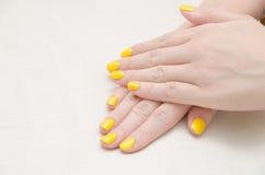 有黄色指甲油的妇女 免版税图库摄影