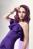 有紫色摆在墙壁附近的头发和一件紫色礼服的性感的妇女 时尚可爱的性感的女孩艺术画象  免版税库存图片