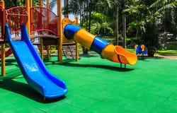 有绿色有弹性橡胶地板的五颜六色的操场孩子的 免版税库存照片