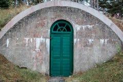 有绿色木门的一个被风化的被成拱形的室外混凝土地下地窖 免版税库存照片