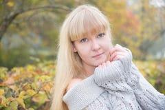有黄色枫叶的白肤金发的女孩 库存照片