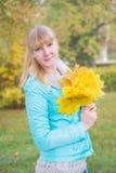有黄色枫叶的白肤金发的女孩 库存图片