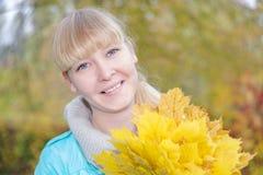 有黄色枫叶的白肤金发的女孩 免版税库存图片