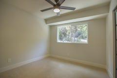 有绿色树吊扇和看法的空的卧室在圣地亚哥房地产射击的窗口外 库存照片
