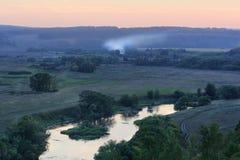 有绿色树的安静的小河和草甸和遥远的烟 免版税库存图片