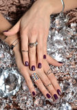 有紫色样式的妇女手擦亮钉子和银色堆积 免版税库存照片