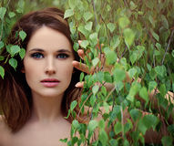 有绿色桦树叶子的美丽的少妇 免版税库存图片