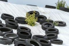 有绿色植物的使用的轮胎在暴风云下的白色小山的 免版税库存照片