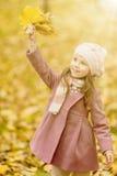 有黄色槭树叶子的小女孩 免版税图库摄影