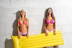 有黄色气垫的两个性感的女孩在晴朗的墙壁上 库存照片