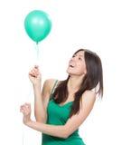 有绿色气球的愉快的女孩作为生日聚会的一个礼物 免版税图库摄影