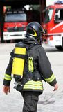 有黄色氧气瓶和盔甲的消防队员 免版税库存照片