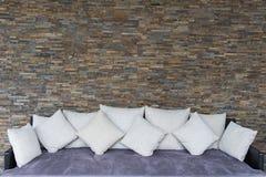 有紫色沙发的现代石墙 免版税库存照片