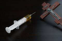 有黄色液体和被迫害的耶稣的注射器木十字架的 免版税库存照片