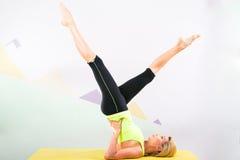 有黄色瑜伽席子的美丽的pilates辅导员 免版税库存照片