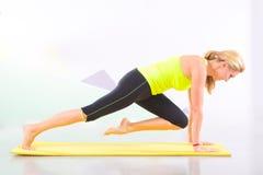 有黄色瑜伽席子的美丽的pilates辅导员 库存照片