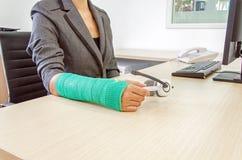 有绿色的受伤的女实业家在举行白色的腕子熔铸了 库存图片