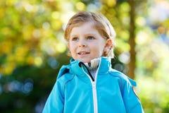 有黄色秋叶的小孩男孩在公园 免版税库存图片