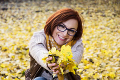 有黄色秋叶的微笑的红头发人妇女 库存照片