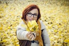 有黄色秋叶的年轻红头发人妇女 图库摄影
