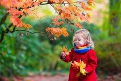 有黄色秋天叶子的小女孩 免版税图库摄影