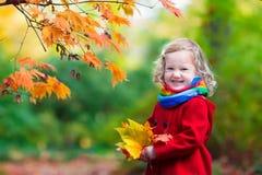 有黄色秋天叶子的小女孩 免版税库存图片