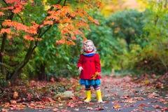 有黄色秋天叶子的小女孩 免版税库存照片
